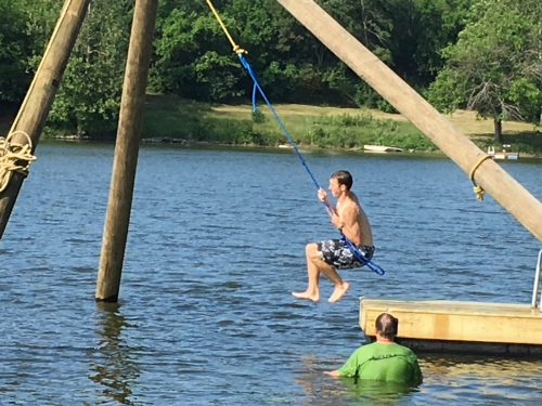 Staff on rope swing in lake