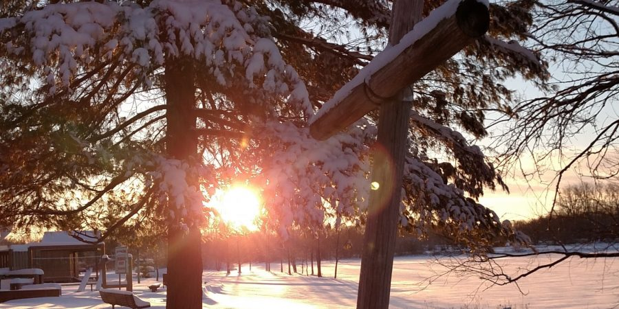 Sunrise behind cross at snow covered Ebenezer