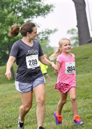 Adult & child participants of 5K running in grass