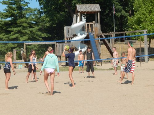 Campers playing volleyball near playground